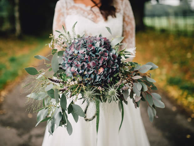 The Flower Style Co used purple and blue hydrangea, green thistles veronica, white nerine, panicum, wax flower, berried eucalyptus and veronica for this dramatic bunch.