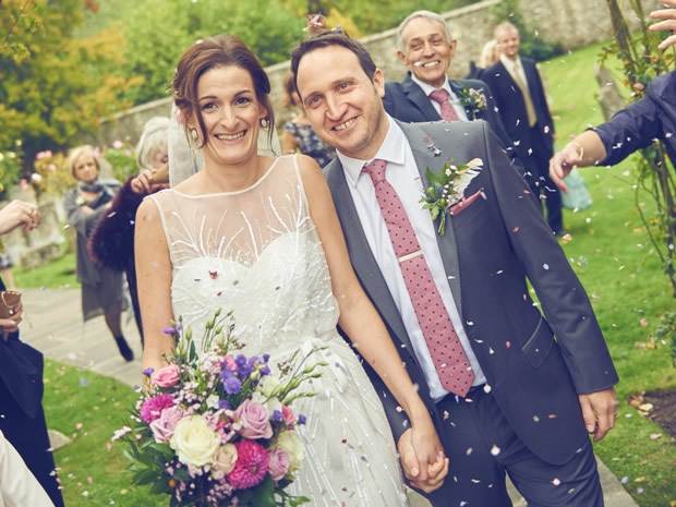 Cath and Huw are showered with confetti after leaving St Mary's Church in Bibury.